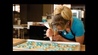Sarah Niebler decorates snowflake cookies at Sunshine & Moons organic bakery